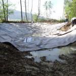 Mise en place d'un feutre protégeant la bâche des éléments tranchants présents dans le sol